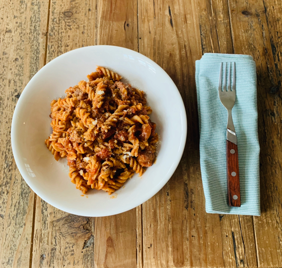 Sausage pasta in a white bowl on a wooden table, with a fork next to it, ready to eat.